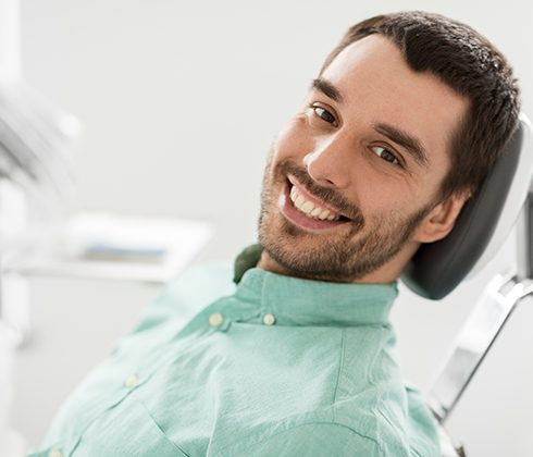 man smiling in exam chair