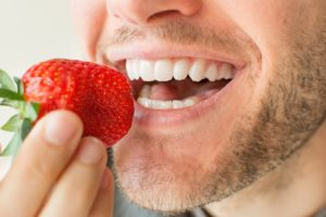 A man eating a strawberry.