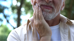 Distressed man holding his jaw in pain