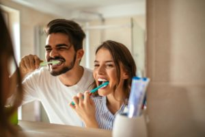 Couple brushing their teeth with tips from a dentist