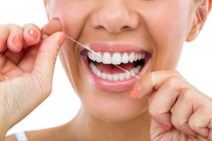 Closeup of woman smiling and flossing