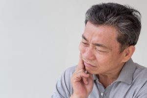 Senior man struggling with problems of ill-fitting dentures