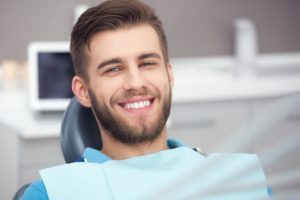 Smiling man in a blue shirt after getting dental implants