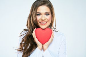 Smiling woman without gum disease holding heart shape
