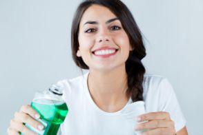 Smiling woman using mouthwash